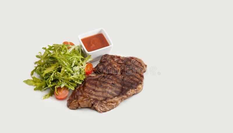 烤利益、蔬菜沙拉蕃茄和红色辣调味汁 烤肉膳食概念 灰色背景,复制空间 库存图片
