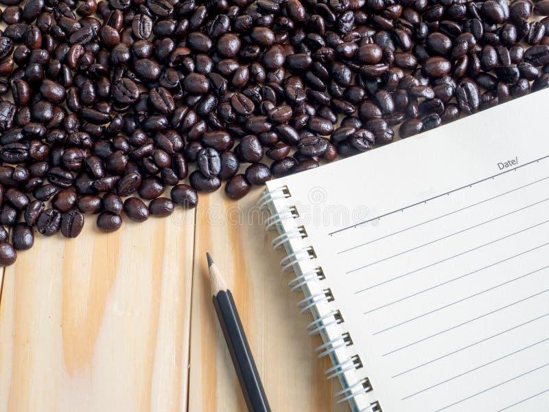 烤咖啡豆和备忘录在木桌上 免版税库存图片