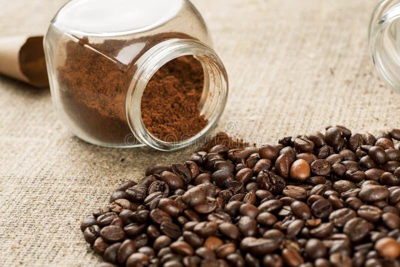 烤咖啡豆和玻璃瓶子用里面碾碎的咖啡 免版税库存照片