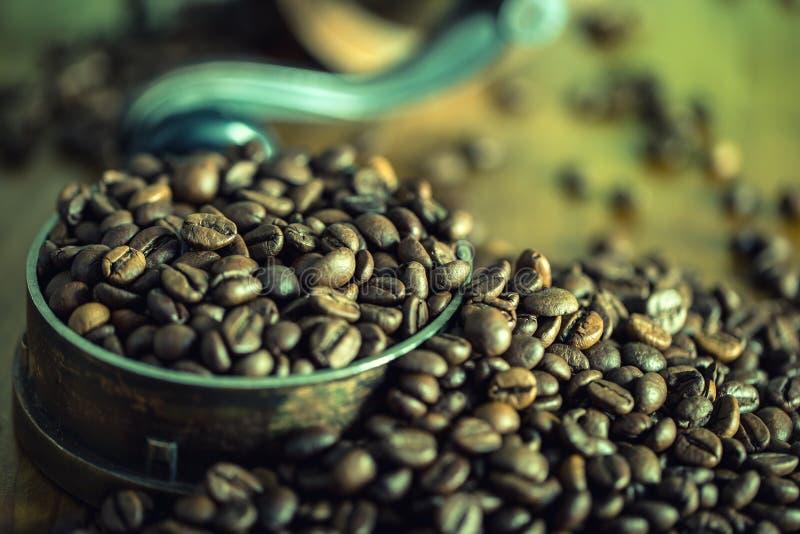 烤咖啡豆在一张木桌上自由地溢出了 在一个盘的咖啡豆碾碎的咖啡的 免版税库存照片