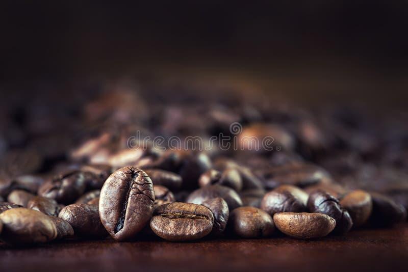 烤咖啡豆在一张木桌上自由地溢出了 免版税库存图片