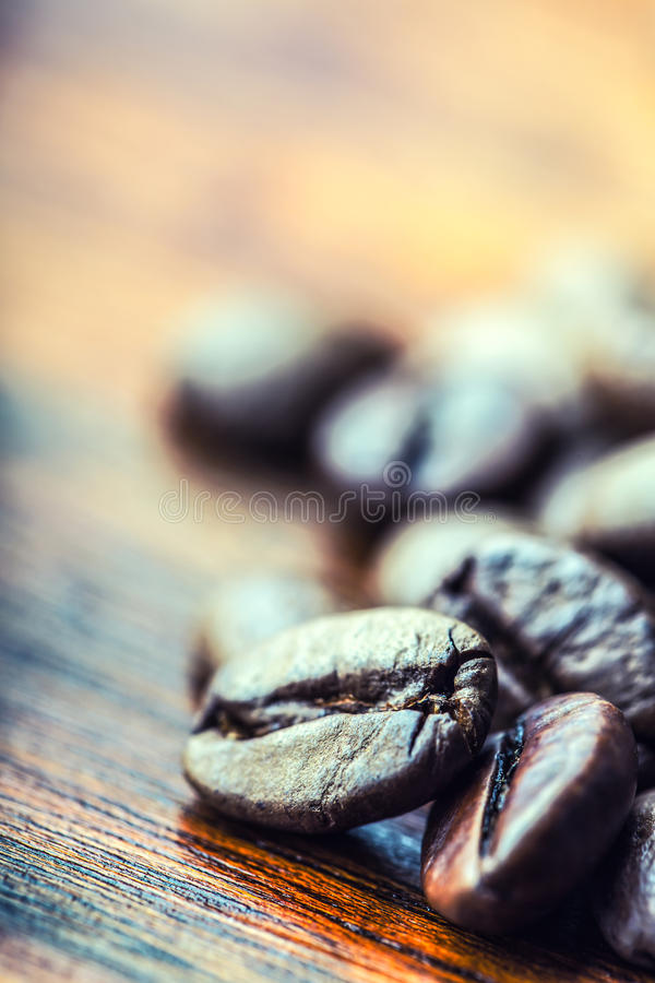 烤咖啡豆在一张木桌上自由地溢出了 库存图片