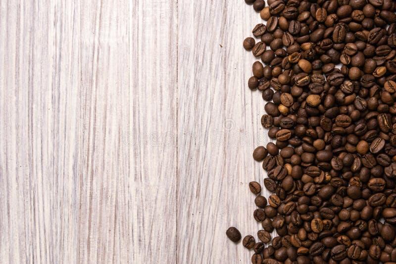 烤咖啡豆散装在轻的木背景的 黑暗的cofee烤了五谷味道芳香咖啡馆,自然coffe商店 免版税库存照片