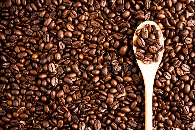 烤咖啡豆背景和纹理与木匙子, co 免版税库存图片