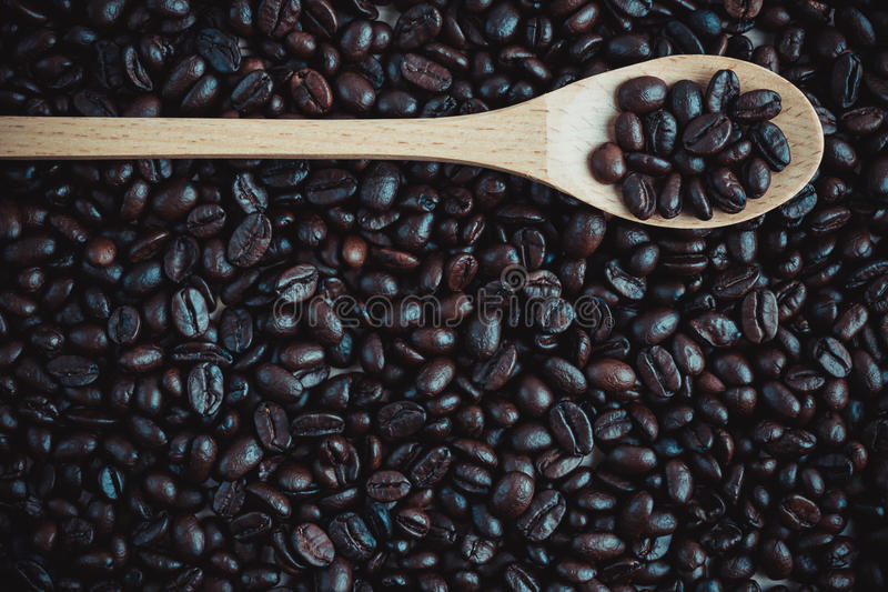 烤咖啡豆背景和纹理与木匙子, co 免版税库存照片