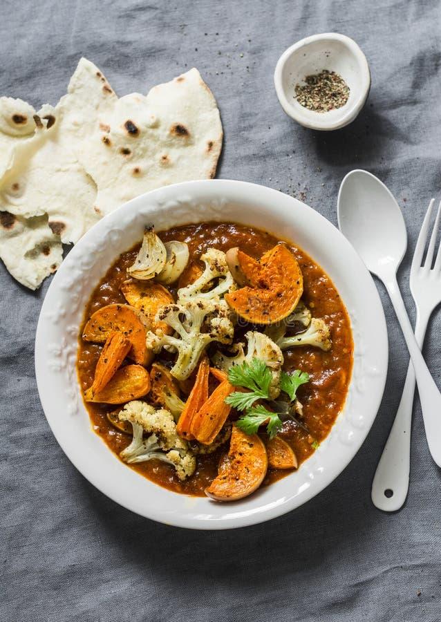 烤咖喱菜 白薯,花椰菜,红萝卜,葱,南瓜用在灰色背景,顶视图的咖喱汁 免版税图库摄影