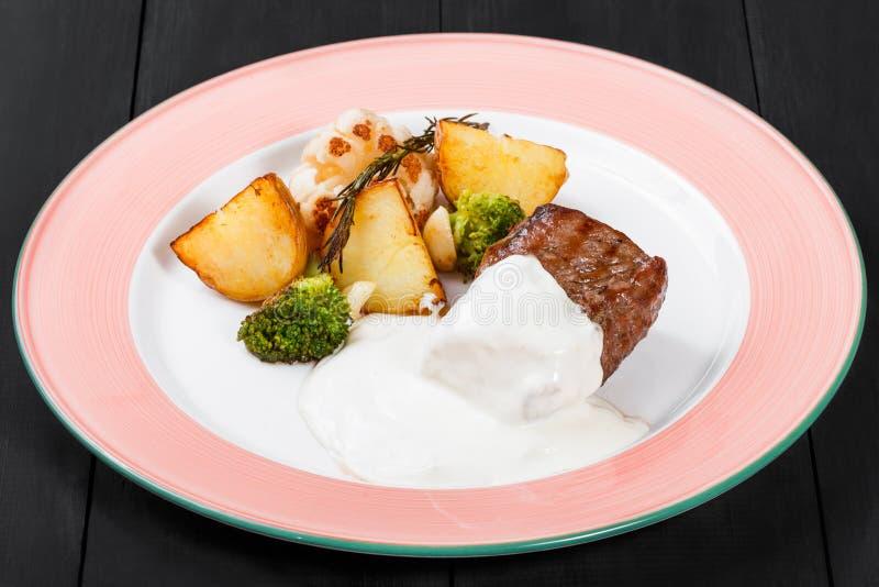 烤土豆用牛肉肉、草本、硬花甘蓝和调味汁在板材在黑暗的木背景 免版税库存图片