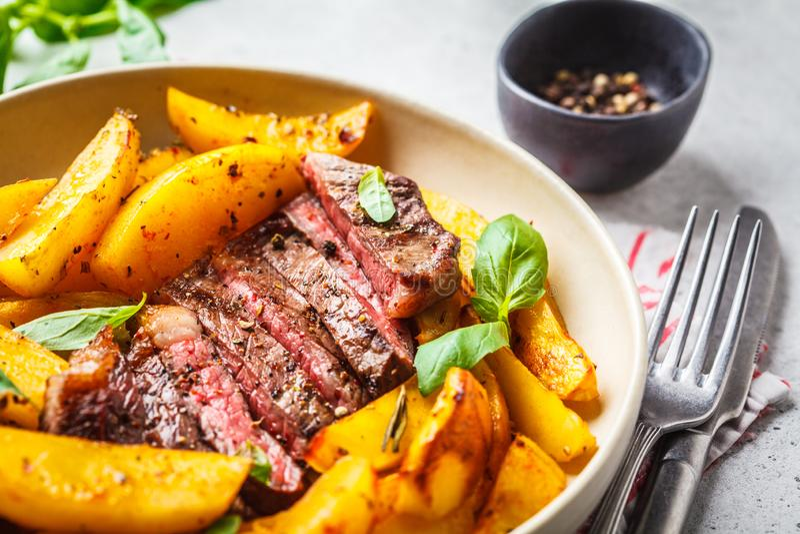 烤在一块白色板材的牛排用土豆和蓬蒿在白色背景 免版税库存照片