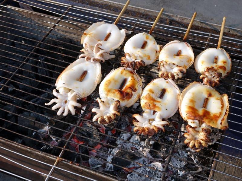 烤在与灼烧的木炭的钢花格木炭火炉的新鲜的白色鱿鱼烤肉的关闭 库存图片