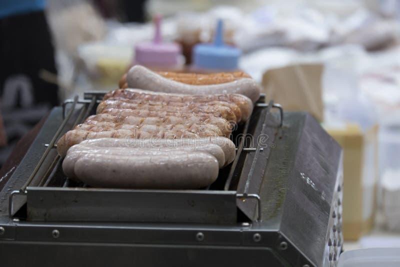 烤在火焰的香肠在格栅 免版税库存图片