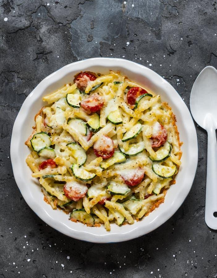 烤夏南瓜和西红柿烘烤了橡皮防水布和乳酪在黑暗的背景,顶视图 素食健康午餐 免版税库存照片