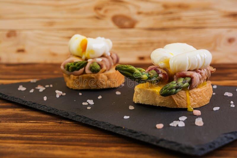 烤多士用在烟肉和荷包蛋的芦笋在木背景 库存照片