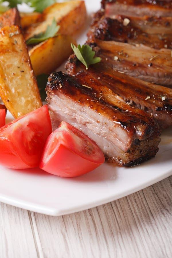 烤宏观猪肉肋骨、土豆和的蕃茄 垂直 免版税图库摄影