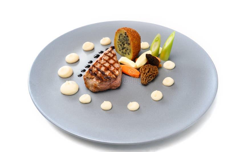 烤幼牛、羊肚菌、菜和用在一块蓝色板材,在a的欢乐被装饰的食家盘的葱种子充塞的一个油煎的 库存图片