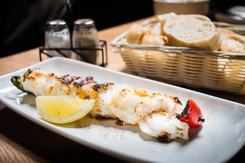 烤或烤冰岛鳕鱼用在白色盘o的柠檬 免版税库存照片