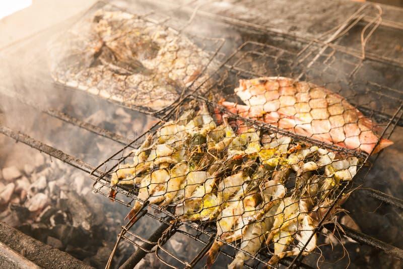 烤新鲜的海鲜:大虾,鱼,章鱼,牡蛎食物背景烤肉/烹调在火的BBQ海鲜 免版税库存照片