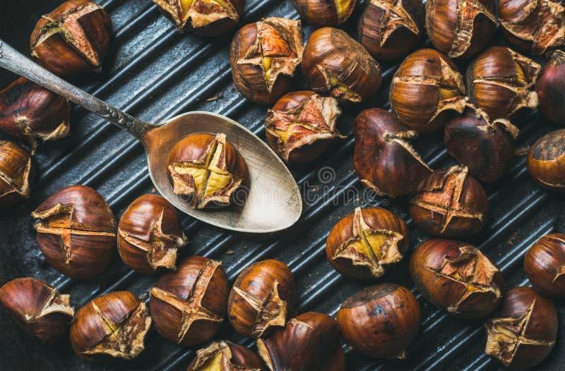 烤栗子和金属葡萄酒匙子特写镜头在平底锅 库存图片