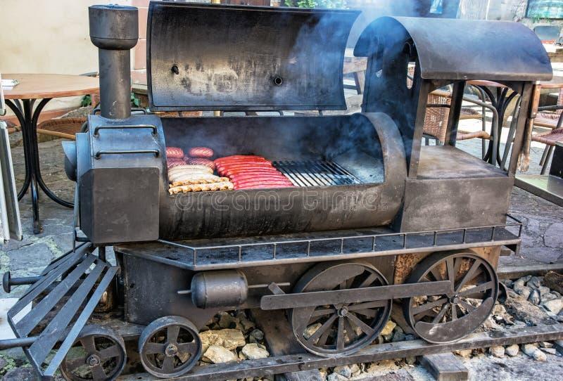 烤格栅用在老蒸汽机车形状的肉  免版税库存图片