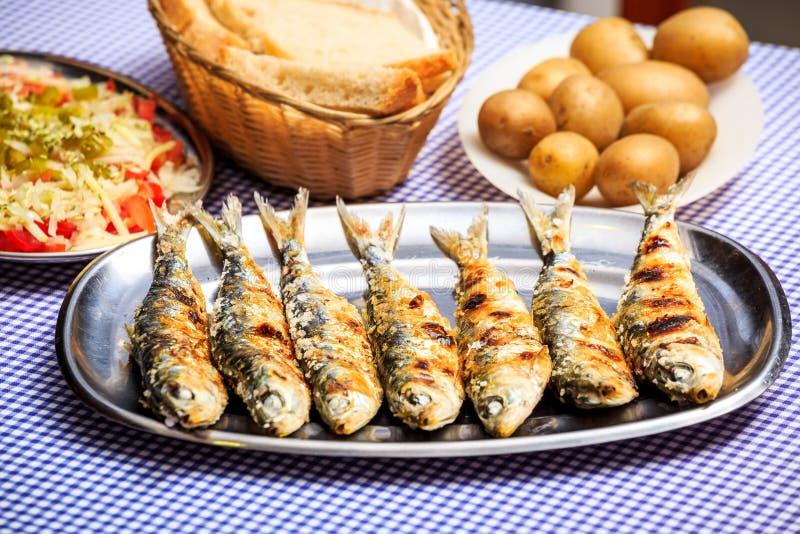 烤沙丁鱼用沙拉、面包和土豆 免版税图库摄影