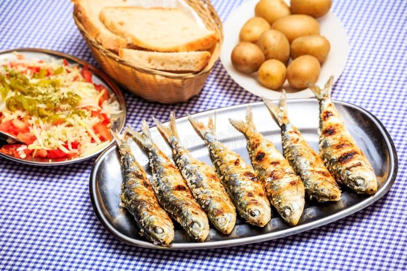 烤沙丁鱼用沙拉、面包和土豆 库存照片