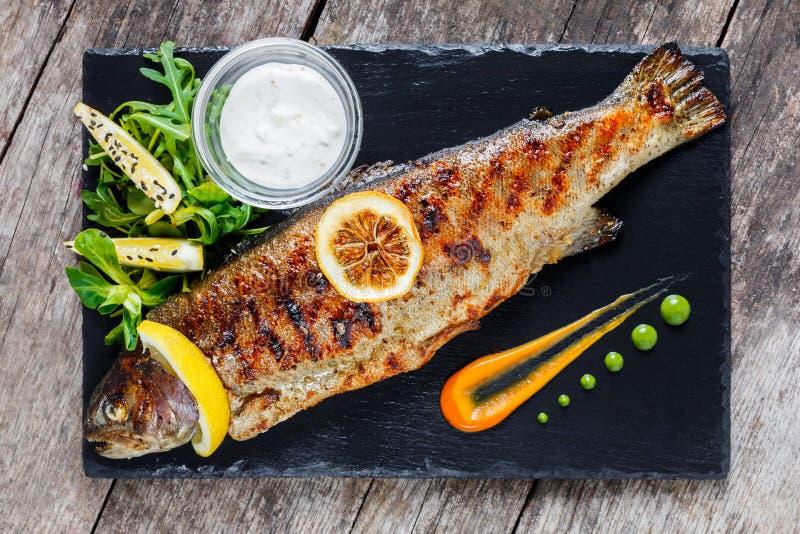 烤海鱼用在石板岩背景关闭的柠檬 健康的食物 顶视图 库存图片