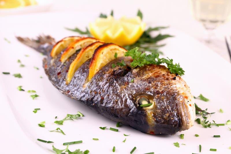 烤海鲷鱼,柠檬,在白色板材的芝麻菜 免版税图库摄影