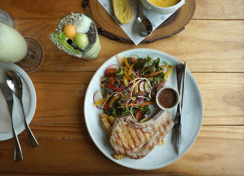 烤炸猪排牛排服务用新鲜的沙拉和蘑菇酱油在木材桌上 库存照片