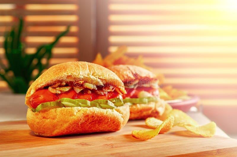 烤热狗或熏肉香肠用油煎的葱和用卤汁泡的黄瓜 筹码查出土豆白色 在木桌上的最后快餐 库存照片
