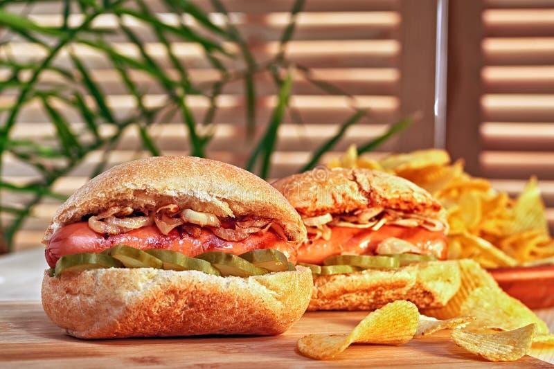 烤热狗或熏肉香肠用油煎的葱和用卤汁泡的黄瓜 筹码查出土豆白色 最后经典快餐 免版税库存照片