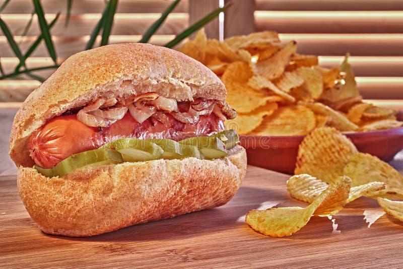 烤热狗或熏肉香肠用油煎的葱和用卤汁泡的黄瓜 筹码查出土豆白色 经典快餐,在木桌上的手抓食物 免版税库存照片
