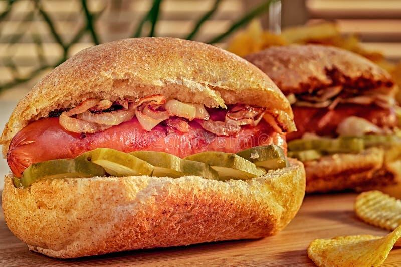 烤热狗或熏肉香肠用油煎的葱 芝加哥样式热狗用芥末、腌汁和葱 筹码查出土豆白色 库存图片
