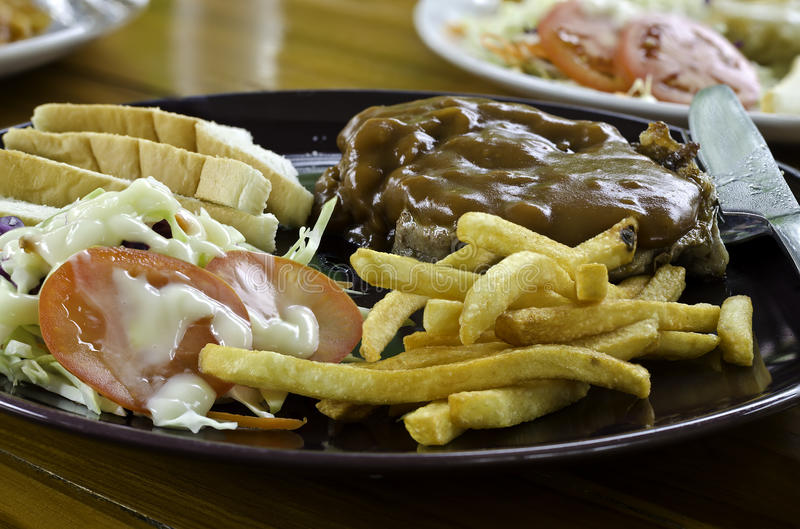烤牛排、炸薯条、面包和菜 免版税库存照片