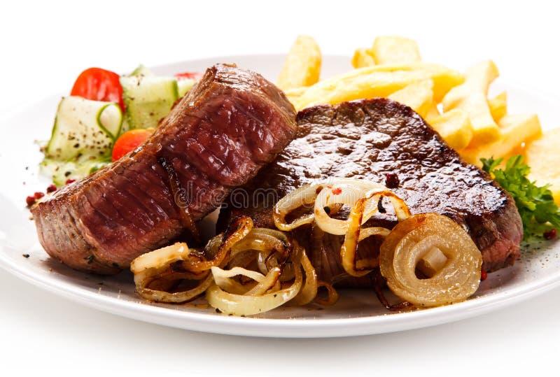 烤牛排、炸薯条和菜 免版税库存照片