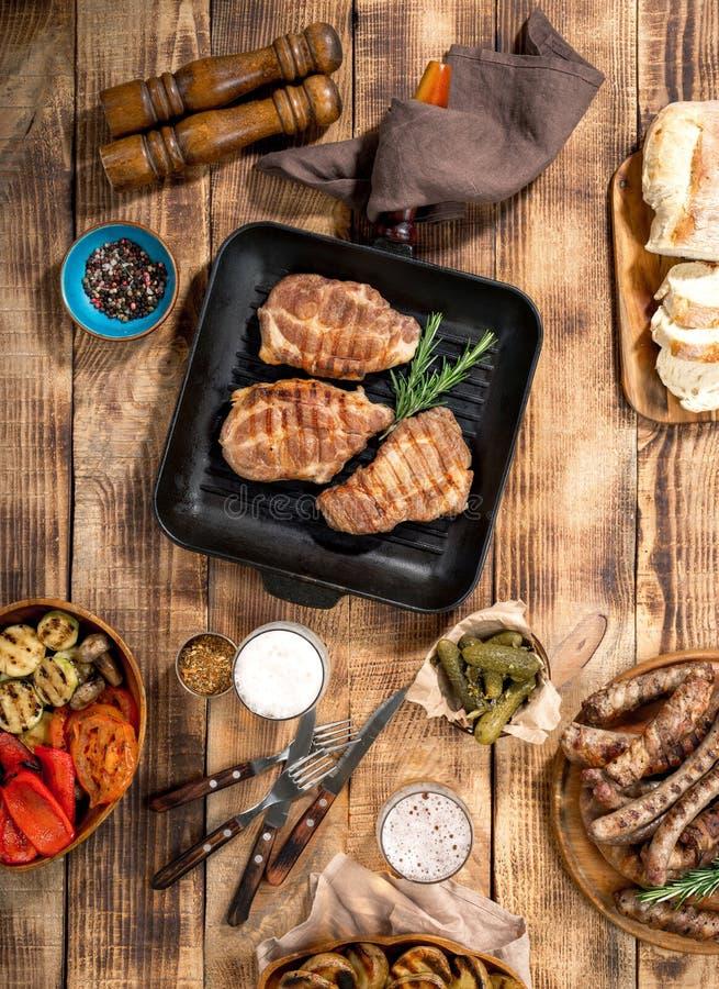 烤牛排、烤香肠、烤菜和贮藏啤酒是 免版税库存图片
