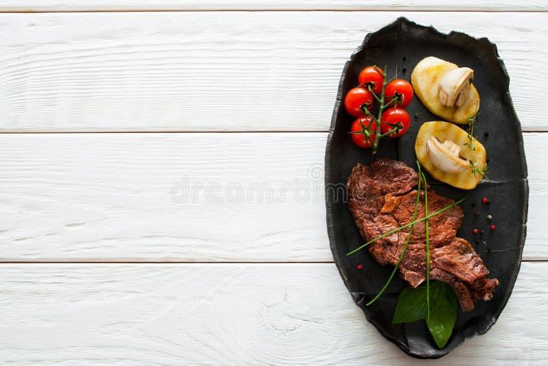烤牛排和土豆,白色木头, copyspace 免版税库存图片