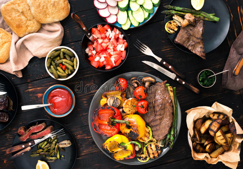 烤牛排和烤菜在木桌上 免版税库存图片