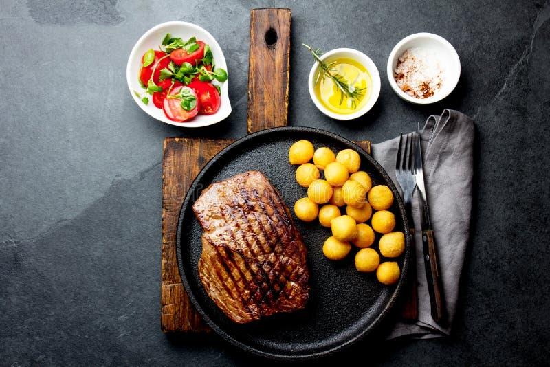 烤牛排在生铁板材服务用蕃茄沙拉和土豆球 烤肉, bbq肉牛里脊肉 免版税库存图片