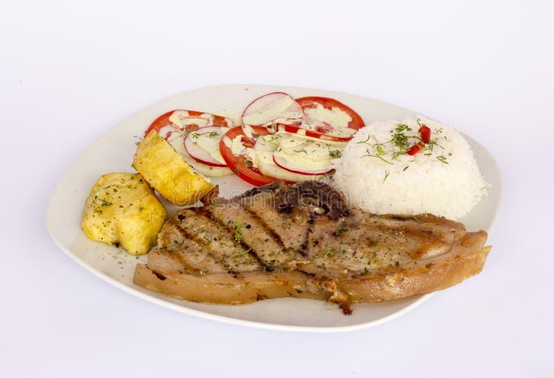 烤牛排猪肉用沙拉,米,土豆,蕃茄 免版税库存图片