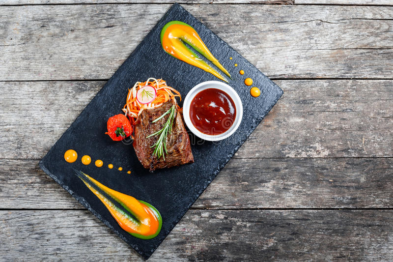 烤牛排用新鲜的沙拉和bbq调味汁在石板岩背景在木背景关闭 断送热肉 免版税图库摄影