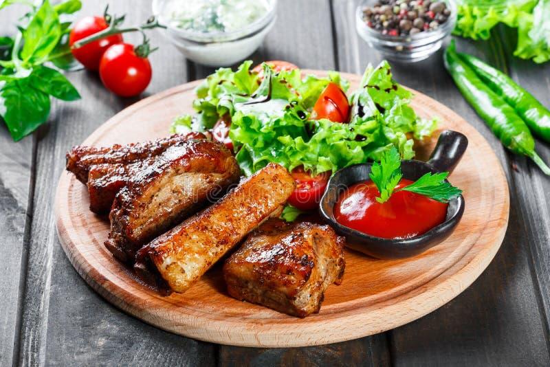 烤牛排用新鲜蔬菜沙拉、蕃茄和调味汁在木切板 免版税库存照片