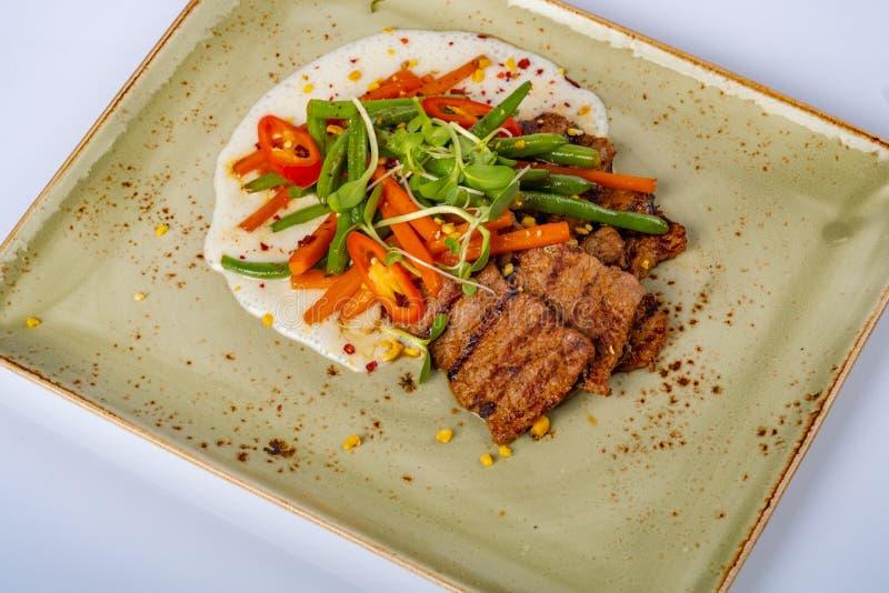 烤牛排用芦笋和红萝卜供食在餐馆 免版税库存图片