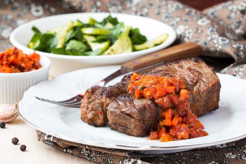烤牛排用辣调味汁调味汁烘干了蕃茄,红辣椒 免版税图库摄影