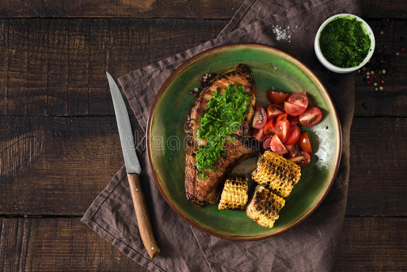 烤牛排用chimichurri调味汁和蕃茄在木ta 库存图片