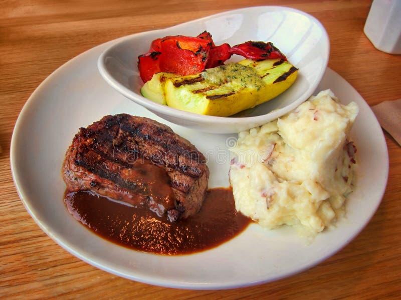 烤牛排,大蒜在餐馆捣碎了土豆和菜在白色板材 免版税库存图片