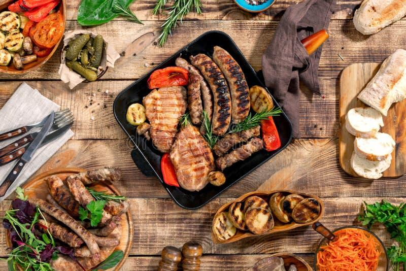 烤牛排,烤香肠,在woode的烤菜 免版税库存图片