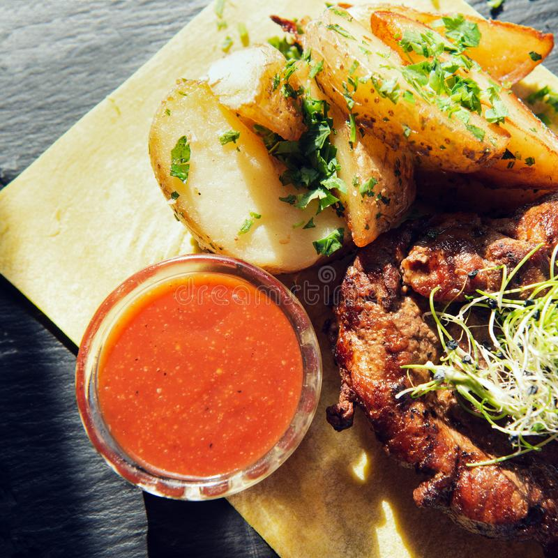 烤牛肉或猪肉牛排在皮塔饼服务用土豆和薤 免版税库存照片