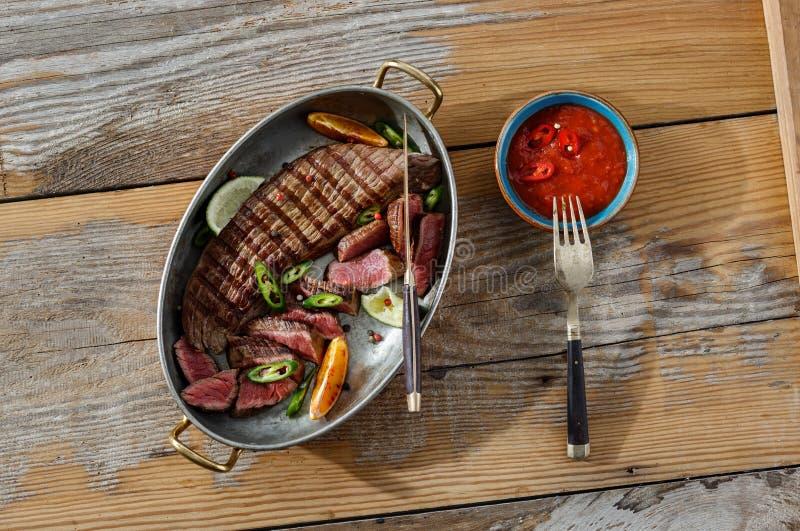 烤牛肉肉供食了平底锅木桌调味汁顶视图 图库摄影
