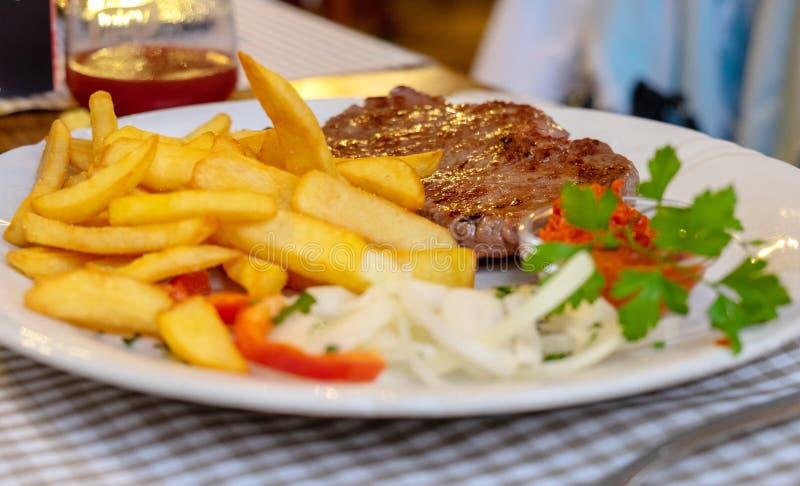 烤牛肉肉和油煎的法国土豆,供食在餐馆 库存图片