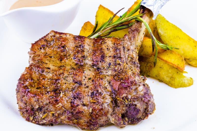 烤猪排和被烘烤的土豆 免版税库存照片
