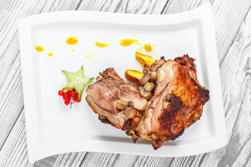 烤猪肉充塞用蘑菇、桃子、阳桃、蔓越桔和甜调味汁在板材在木背景 库存照片